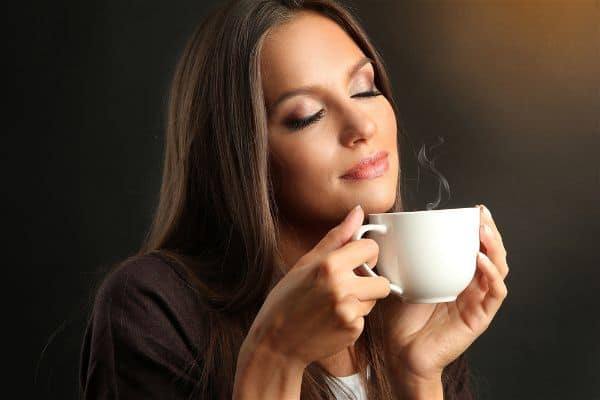Woman smelling dark roast coffee aroma