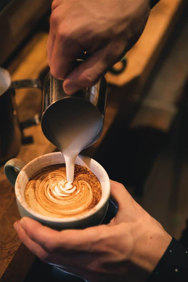 pouring milk on coffee